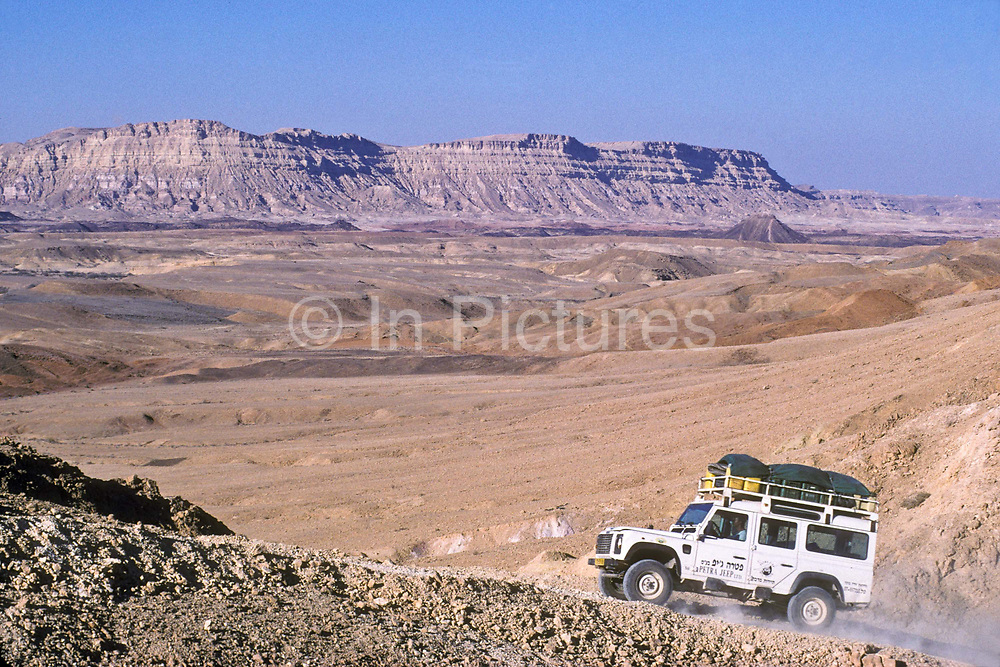 A land rover drives through the worlds largest natural crater meassuring 40 x 10 Kms wide in the Negev desert, Israel.