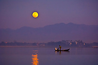 Boats crosses Taungthaman Lake, next to the U-Bein Bridge, as the moon rises, Amarapura (near Mandalay), Myanmar (Burma)