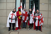 Medieval knights with a dragon in sunglasses on an afternoon pub crawl on St Georges Day on 23rd April 2018 in London, England, United Kingdom. Wearing chainmail, St Georges Cross shields and flags, this type of dressing up has become popular as a sign of patriotism and fun as groups go out drinking on Englands national day.