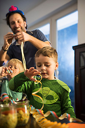 Father and son blowing paper streamers at a party
