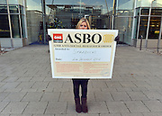 © Licensed to London News Pictures. 04/12/2012. London, UK Lauren Tinney from the GMB union holds up a placard awarding Starbucks an 'ASBO for antisocial behaviour' after being prevented from handing it in to the headquarters reception. GMB union members demonstrate outside Starbucks Head Quarters on Chiswick High Road, London, over complaints that the coffee firm does not pay its staff the Living Wage, today 4th December 2012. Photo credit : Stephen Simpson/LNP