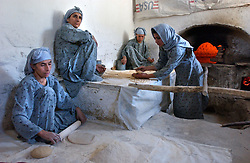 Afghan widows make bread in a bakery set up to help vulnerable families by subsidizing the cost of bread in Kabul, Afghanistan September 10,2002. (Photo by Ami Vitale/Getty Images)