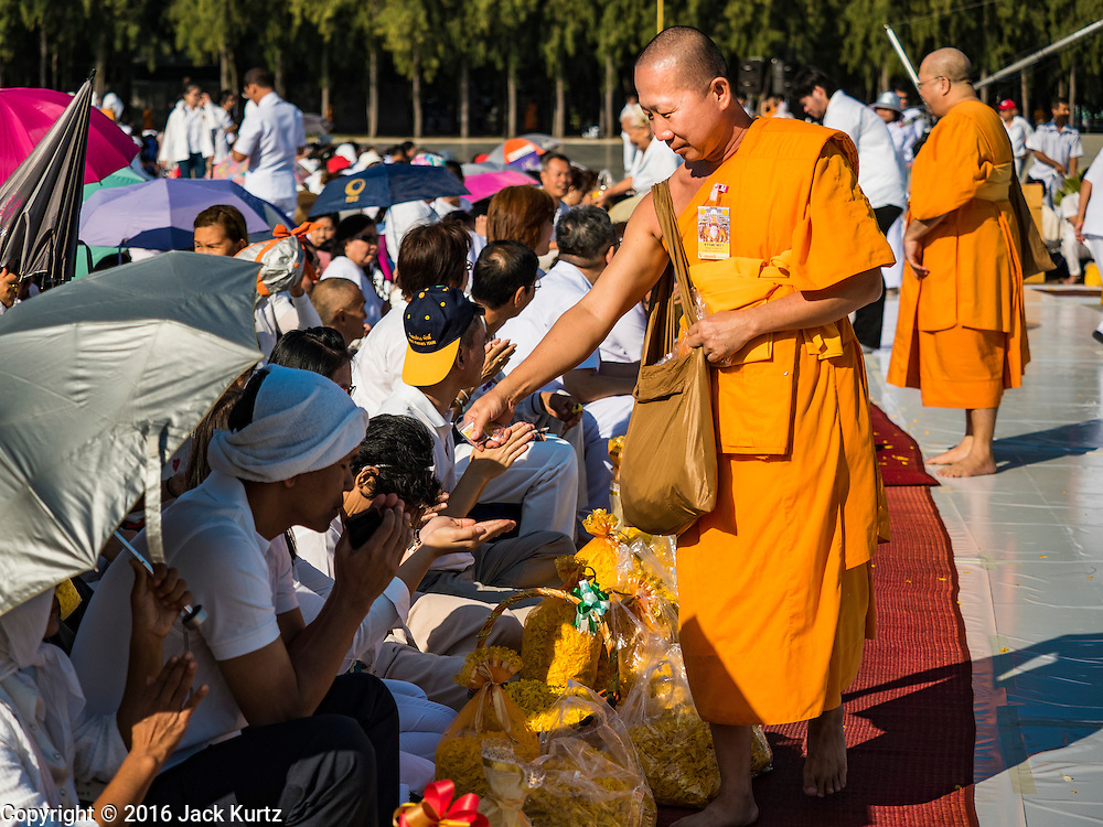 """02 JANUARY 2016 - KHLONG LUANG, PATHUM THANI, THAILAND:  A Buddhist monk passes out amulets before the pilgrimage at Wat Phra Dhammakaya on the first day of the 5th annual Dhammachai Dhutanaga (a dhutanga is a """"wandering"""" and translated as pilgrimage). More than 1,300 monks are participating pilgrimage through central Thailand. The purpose of the pilgrimage is to pay homage to the Buddha, preserve Buddhist culture, welcome the new year, and """"develop virtuous Buddhist youth leaders."""" Wat Phra Dhammakaya is the largest Buddhist temple in Thailand and the center of the Dhammakaya movement, a Buddhist sect founded in the 1970s. The monks are using busses on some parts of the pilgrimage this year after complaints about traffic jams caused by the monks walking along main highways.         PHOTO BY JACK KURTZ"""