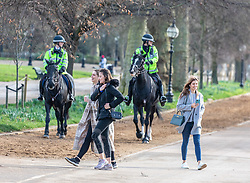"""© Licensed to London News Pictures. 23/02/2021. London, UK. Police on horse back patrol Hyde Park, London despite the pending easing of lockdown while members of the public enjoy the sunshine and mild temperatures this afternoon as weather forecasters predict a warm and sunny week ahead with highs of 17c in the South East. Yesterday, Prime Minister Boris Jonson announced his """"Roadmap Map' out of Lockdown with a gradual easing of Covid-19 restrictions with shops, pubs and gyms to open by April, Rule of Six and schools back by March and nightlife back by June. Photo credit: Alex Lentati/LNP"""