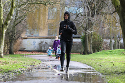 © Licensed to London News Pictures. 05/02/2021. London, UK. A jogger runs through a puddle of water in Chestnuts Park, north London. Part of the footpath in the park is flooded following heavy overnight rain in London. According to the Met Office, snow is forecast for the weekend. Photo credit: Dinendra Haria/LNP