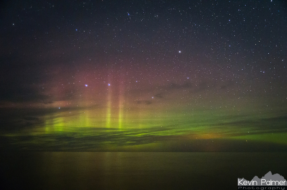 The northern lights are reflected in the waters of Lake Superior as clouds move in. During a very cloudy week in Michigan's Upper Peninsula, there was only one night that was partially clear. After hiking 10 miles to a campsite on the lake, I waited for it to get dark. The aurora was initially visible as twilight ended, but then it faded away. After midnight it became brighter, and the colorful pillars rose up and drifted from left to right.<br />