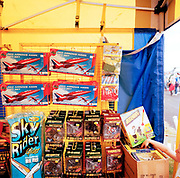 A young lad shows interest in Airfix models incl the 'Red Arrows', Britain's Royal Air Force aerobatic team. In the far right corner of the picture, we see the boy's hand reaching into a box of toys on sale at a stall at Fairford air show (RIAT). Airfix is a UK manufacturer of plastic scale model kits of aircraft and other subjects. In Britain, the name Airfix is synonymous with the hobby and was founded in 1939 by a Hungarian businessman Nicholas Kove, initially manufacturing rubber inflatable toys. Red Arrows Hawks throughout their calendar of appearances at air shows and fly-pasts across the UK and a few European venues. Since 1965 the squadron have flown over 4,000 shows in 52 countries and are an important part of Britain's summer events where aerobatics aircraft perform their manoeuvres in front of massed crowds.