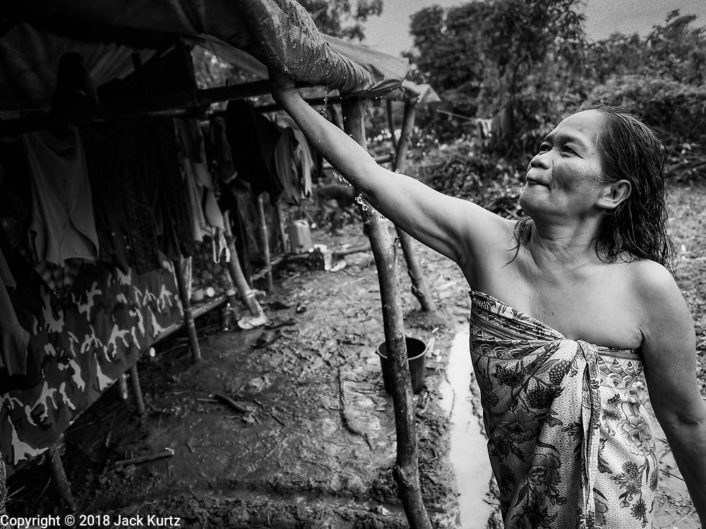 26 JANUARY 2018 - SANTO DOMINGO, ALBAY, PHILIPPINES: A woman who was evacuated from the Mayon volcano knocks rainwater off the roof of the tent she's living in in a field near Santo Domingo. Mayon Volcano was relatively quiet Friday, but the number of evacuees swelled to nearly 80,000 as people left the side of  the volcano in search of safety. There are nearly 12,000 evacuees in Santo Domingo, one of the most impacted communities on the volcano. The number of evacuees is impacting the availability of shelter space. Many people in Santo Domingo, on the north side of the volcano, are sleeping in huts made from bamboo and plastic sheeting. The Philippines is now preparing to house the volcano evacuees for up to three months.        PHOTO BY JACK KURTZ