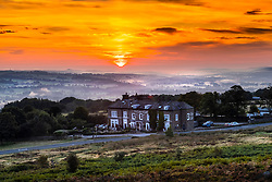 © Licensed to London News Pictures. 17/09/2021. Ilkley UK. The sun breaks through the low lying mist this morning & rises over the Cow & Calf pub high up on Ilkley moor in Yorkshire. Photo credit: Andrew McCaren/LNP