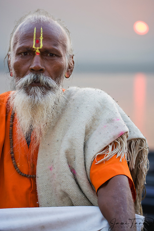 A holy man stares into the camera as he sits comfortably on a ghat along the Ganges River as the sun sets behind him, Varanasi, Uttar Pradesh, India