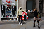During a windy afternoon, a sandwich board man returns a dropped scarf for a young woman in central London.