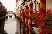 Canal in Venice Italy with flowers and striped boat bumpers to protect the dock.