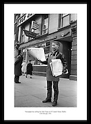 Newspaper boy selling the Irish Times on O'Connell Street, Dublin.<br /> <br /> 12th February 1963<br /> <br /> 12/02/1963