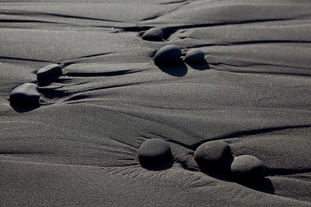 Water erosion and rounded pebbles form an abstract design in the sand at Kalaloch Beach, Olympic National Park, Washington.