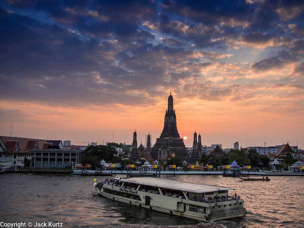 """19 DECEMBER 2013 - BANGKOK, THAILAND:  A tour boat in front of Wat Arun at the end of the day. Wat Arun Ratchawararam Ratchawaramahawihan or Wat Arun (""""Temple of Dawn""""), a Buddhist temple (wat) in Bangkok Yai district of Bangkok, on the Thonburi side of the Chao Phraya River. The temple derives its name from the Hindu god Aruna, often personified as the radiations of the rising sun. Wat Arun is among the best known of Thailand's landmarks and the first light of the morning reflects off the surface of the temple with pearly iridescence. Although the temple had existed since at least the seventeenth century, its distinctive Khmer style prang (spires) were built in the early nineteenth century during the reign of King Rama II.        PHOTO BY JACK KURTZ"""