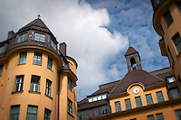 Rooftop of a yellow-orange building in Stockholm, Sweden against a blue cloudy sky