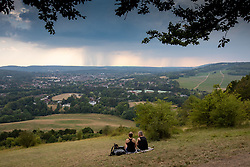 © Licensed to London News Pictures. 12/08/2020. Surrey, UK. Calm before the storms. Picnickers look at the dramatic thunder clouds as they loom over Box Hill in Surrey as the tropical heatwave continues to hit England with temperatures in excess of 34c today. Weather forecasters have predicted that thunderstorms with heavy rain are likely to hit Surrey and London later tonight with the Met Office issuing a yellow weather warning for thunderstorms in the South East of England with risk of flooding and travel disruption. Photo credit: Alex Lentati/LNP