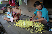 Women from the Kenyah tribe making traditional bags from plastic instead of rattan, which would be found in the rain forest...Sungai Asap Longhouse community where Long Geng Kenyah community was forcibly resettled after their homes where flooded by the Bakun Dam. Home of the Kenyah native people who once lived in Long Geng, which was flooded by the Bakun Dam. Their community is now dispersed between Sungai Asap, Long Lewan and floating longhouses on the Bakun reservoir. Bakun Belaga region, Sarawak Borneo 2012..The huge Petronas Sabah-Sarawak pipeline is being built across the Borneo rainforest through native areas. Petronas is the government cash cow which funds about 45% of its budget. New roads are being built, though much of the transport follows the existing roads and infrastructure created by logging. Whilst the government heralds the project as a source of jobs for local people, it is unlikely to bring much but wanton damage to rainforest habitat and paving the way for further deforestation by oil palm plantations. ..Borneo native peoples and their rainforest habitat revisited two decades later: 1989/1991-2012. ..Sarawak's primary rainforests have been systematically logged over decades, threatening the sustainable lifestyle of its indigenous peoples who relied on nomadic hunter-gathering and rotational slash & burn cultivation of small areas of forest to survive. Now only a few areas of pristine rainforest remain; for the Dayaks and Penan this spells disaster, a rapidly disappearing way of life, forced re-settlement, many becoming wage-slaves. Large and medium size tree trunks have been sawn down and dragged out by bulldozers, leaving destruction in their midst, and for the most part a primary rainforest ecosystem beyond repair. Nowadays palm oil plantations and hydro-electric dam projects cover hundreds of thousands of hectares of what was the world's oldest rainforest ecosystem which had some of the highest rates of flora and fauna endemism, species found