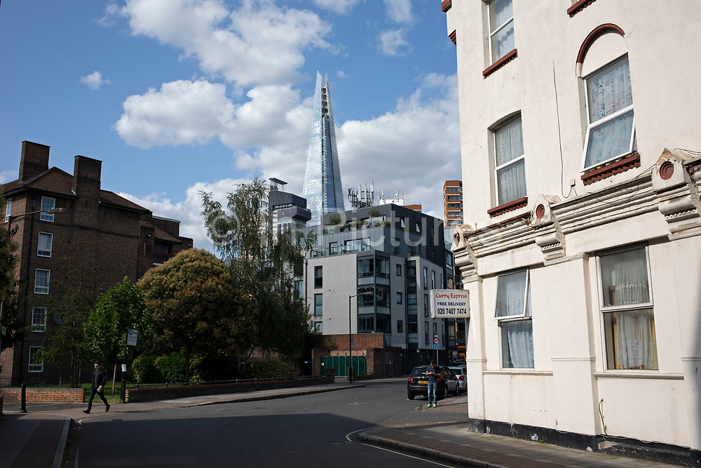 View looking towards The Shard through housing in South London, England, United Kingdom. The Shard, also referred to as the Shard of Glass, Shard London Bridge and formerly London Bridge Tower, is an 87-storey skyscraper in London that forms part of the London Bridge Quarter development.