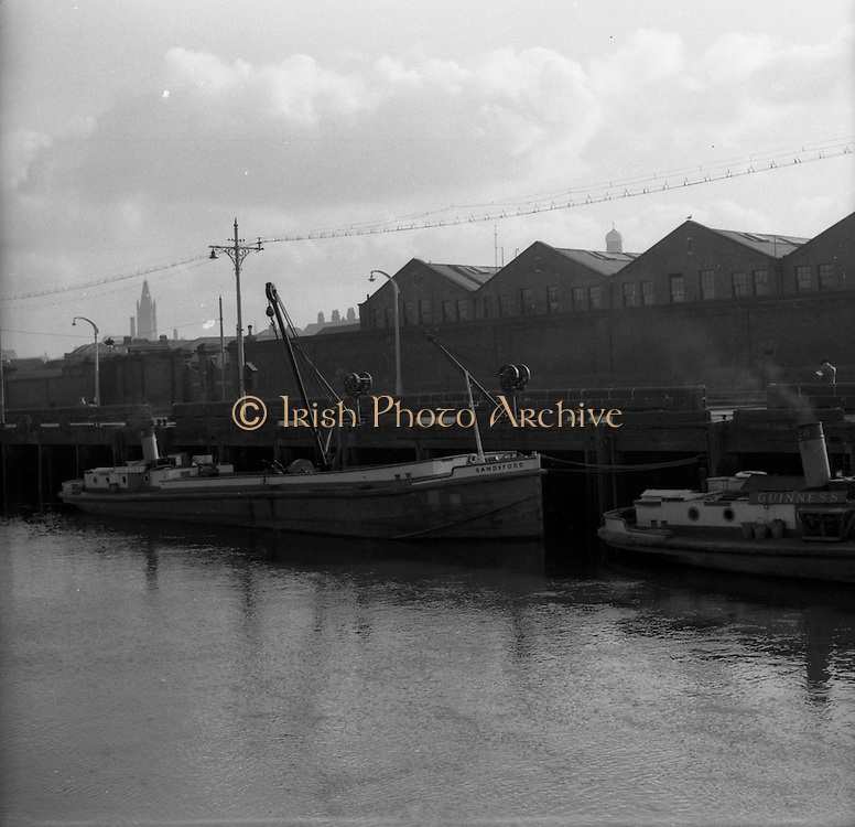 """05/03/1957<br /> Scenes on the Liffey River, Dublin at Guinness's Wharf, the Guinness barge """"Sandyford"""" tied up outside the brewery."""
