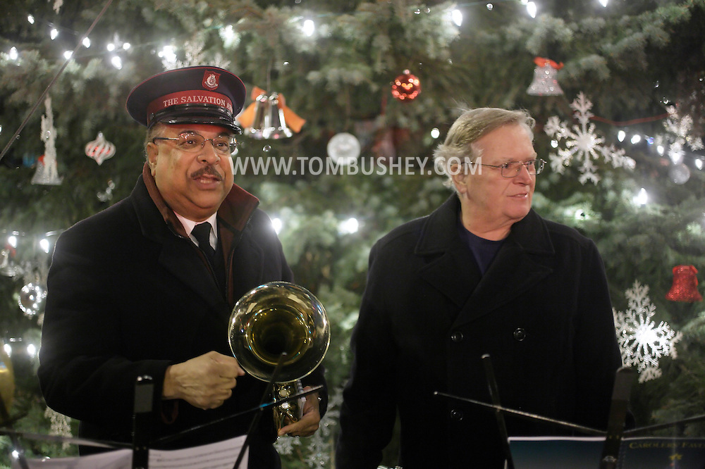 Newburgh, New York- A member of a Salvation Army band, at left, talks to the crowd after playing music during the Christmas tree lighting ceremony on Broadway on the night of Dec. 14, 2011.