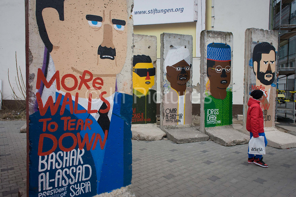 """World dictators (incl Syrian President Bashir al-Assad) adorn old sections of the old Berlin Wall opposite the former Checkpoint Charlie, the former border between Communist East and West Berlin during the Cold War. The Berlin Wall was a barrier constructed by the German Democratic Republic (GDR, East Germany) starting on 13 August 1961, that completely cut off (by land) West Berlin from surrounding East Germany and from East Berlin. The Eastern Bloc claimed that the wall was erected to protect its population from fascist elements conspiring to prevent the """"will of the people"""" in building a socialist state in East Germany. In practice, the Wall served to prevent the massive emigration and defection that marked Germany and the communist Eastern Bloc during the post-World War II period."""