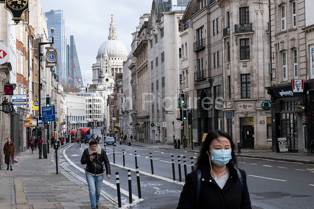 Quiet scene with very few people or vehicles about looking along Fleet Street towards the City of London and St Pauls Cathedral as the national coronavirus lockdown three continues on 29th January 2021 in London, United Kingdom. Following the surge in cases over the Winter including a new UK variant of Covid-19, this nationwide lockdown advises all citizens to follow the message to stay at home, protect the NHS and save lives.