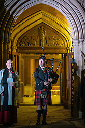 © Licensed to London News Pictures. 11/11/2018. Manchester, UK. A lone piper plays during a service of remembrance for those killed in war , is held at 6am outside Manchester Cathedral , on the morning of the 100th anniversary of Armistice Day , marking the end of the First World War . Photo credit: Joel Goodman/LNP