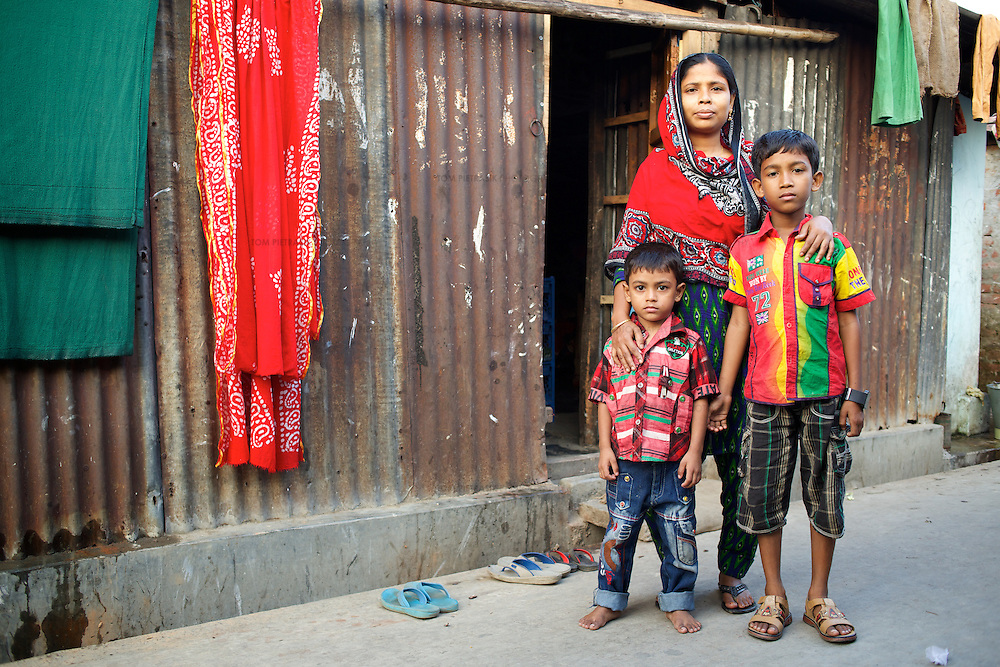 """Jahanara with her two sons Jahidul Islam, age 9 and Jahirul Islam, age 5, outside their home in 36 Bari Colony. <br /> <br /> Jahanara works as a tailor to supplement her husband's income as a construction worker. She volunteers for NGO forum as a health and hygiene promoter working with female adolescents in the slum. A passionate advocate of hand-washing to both adults and children, she's seeing the result of her efforts: """"I like doing the work that I do, the fact that people can stay healthy. I like the result of my work."""" She's also involved in promoting drain clearing. """"Before, the latrines and drains were very dirty. Now, it's a lot better but there's so much more to do."""" <br /> <br /> Jahanara Akhter, age 27, is a resident of 36 Bari Colony, a slum in Mymensingh. Oxfam are working with partners NGO Forum to support residents of 36 Bari Colony in health promotion and disaster preparedness.<br /> <br /> Photo: Tom Pietrasik<br /> Mymensingh, Bangladesh<br /> November 20th 2014"""