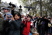 Asian tourists take pictures during the Lord Mayor's Show in London.