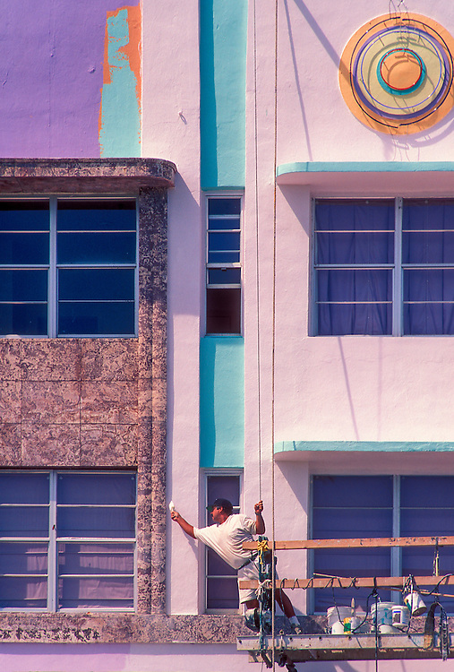 """In the early 1990s, during Miami's historic South Beach Revival, a worker repaints the Art Deco-style Cardozo Hotel, designed in 1939 by Henry Hohauser. <br /> <br /> This Tropical Deco landmark on Miami Beach's Ocean Drive features dyed keystone on the facade (at left) and so-called """"eyebrows"""" or sunshades over the windows."""