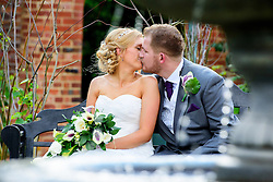Bride and Groom sharing a kiss by the water feature in the beautiful Knebworth House Gardens