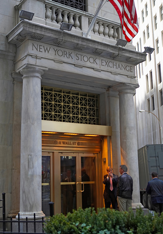 Businessmen taking a break outside the side door of the New York Stock Exchange
