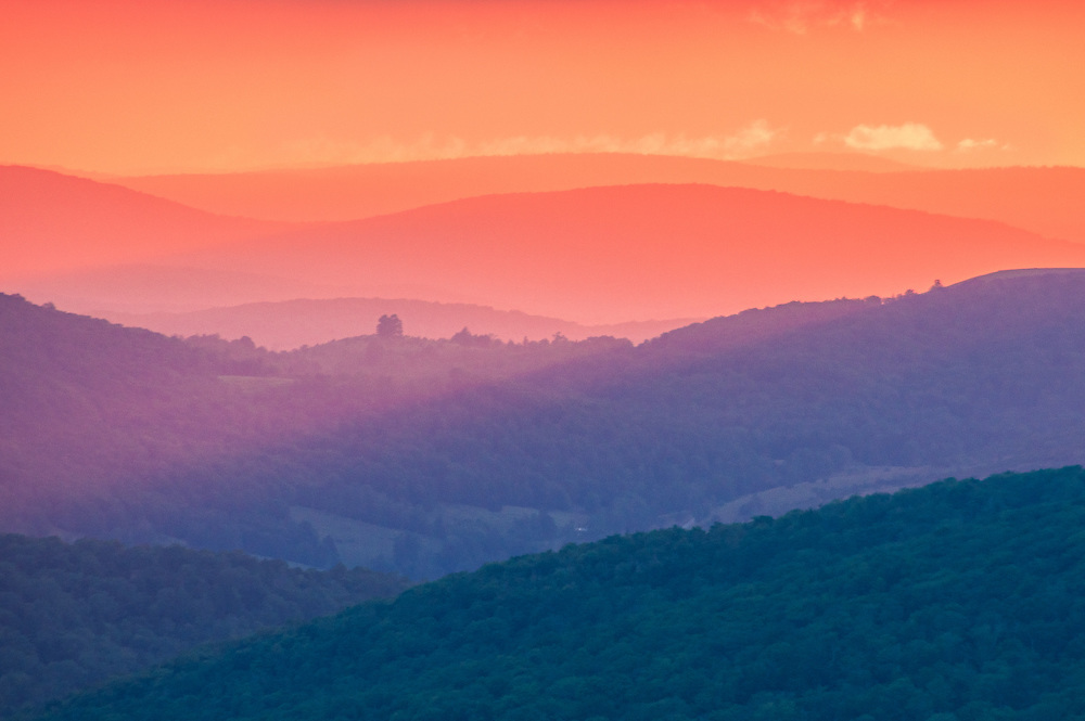 Viewed atop Spruce Knob, the highest point in West Virginia, the distant mountains that cut through the Allegheny Front become colorized by the sun's rays and hazy mountain air mixing with the palate of dark monochromatic blue mounds of earth, brushing across ridge lines creating purple before fading to a blaze of orange and yellows.