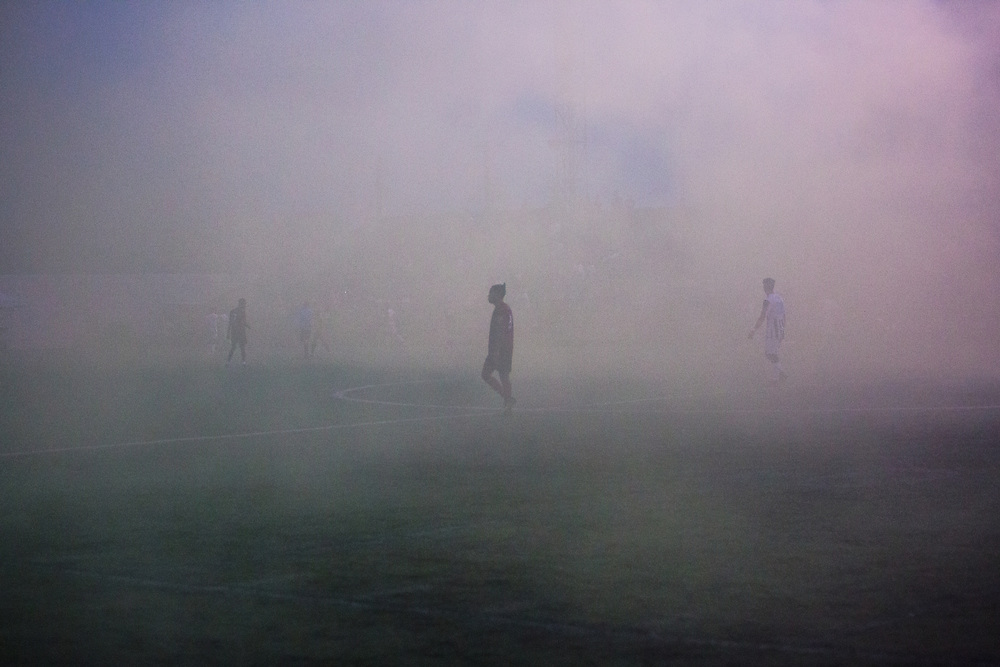 Detroit City players wander through the smoke from their supporters' section after a 90th minute goal was waved offside during Detroit City's match against Kalamazoo FC at Keyworth Stadium in Hamtramck, Mich. on June 23, 2018.