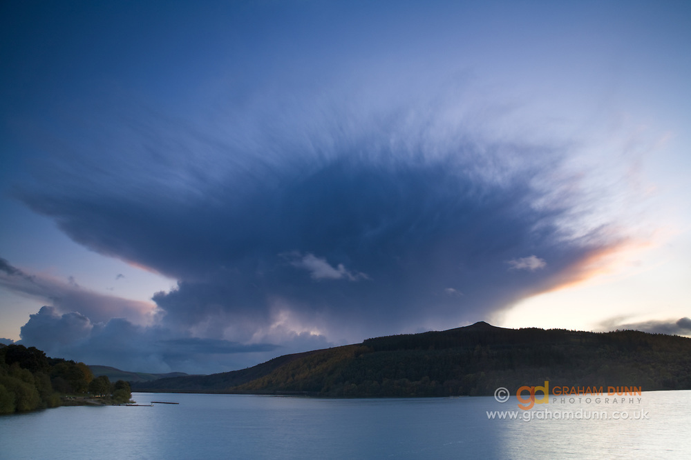A dramatic cloud forms over Win Hill and Ladybower Reservoir, the largest mass of water in the Peak District. A dusk landscape scene in Derbyshire, England, UK.