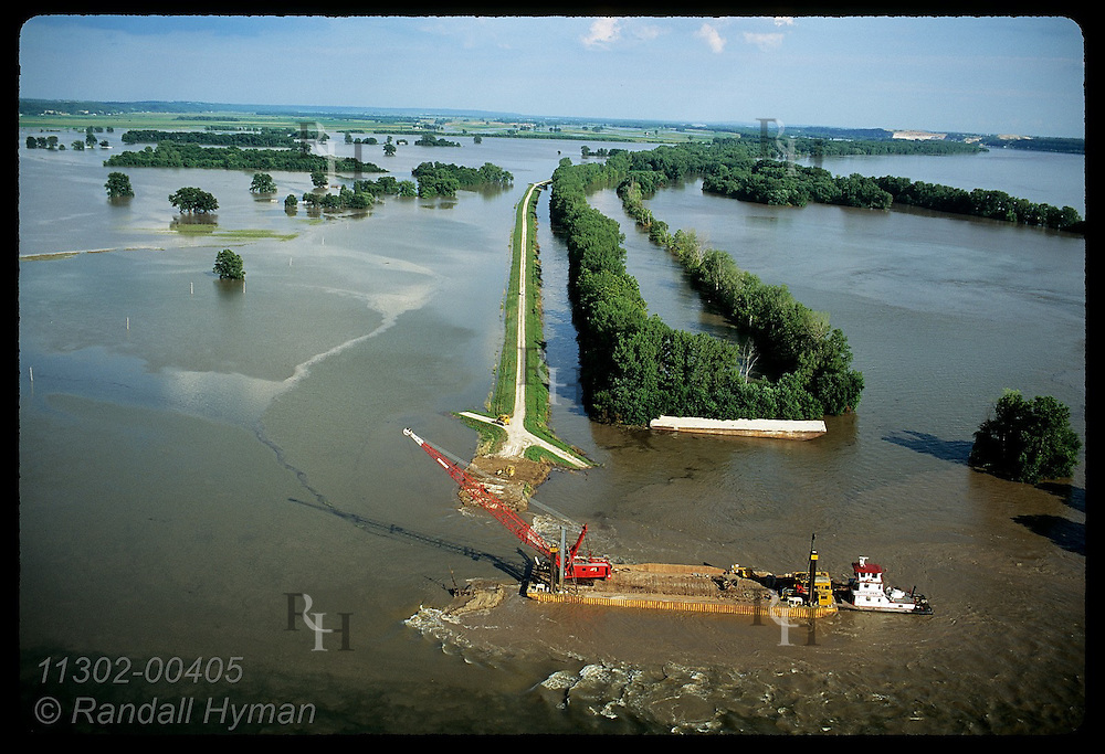 Aerial:crane on barge cuts hole in Mississippi's levee to drain floods on 8/3/93; Prairie Rocher Illinois