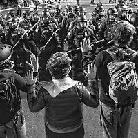 ORIG 8/12/20 Members of local clergy raise their hands as U.S. Border Patrol officers begin to advance towards the buses at Crane Shed Commons in Bend, Ore.,  on Wednesday, Aug. 12, 2020.