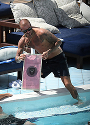 Shirtless David Beckham celebrates his new team, Inter Miami, a he has a few cocktails and takes a dip in the pool in Miami. The new team owner was seen indulging in plenty of celebratory cocktails, taking photos of his new team logo, noshing on a burger and fries, and engaging with a pretty brunette in between taking refreshing dips in the pool. 05 Sep 2018 Pictured: David Beckham; Inter Miami. Photo credit: MEGA TheMegaAgency.com +1 888 505 6342