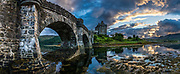 Stone footbridge to Eilean Donan Castle at sunset, in Kintail National Scenic Area, Scotland, United Kingdom, Europe. This picturesque island stronghold sits where three sea lochs meet at the village of Dornie in the western Highlands (Loch Duich, Loch Long, and Loch Alsh). Since restoration of the 1200s castle in the early 1900s, a footbridge connects the island to the mainland. The island is named after Donnán of Eigg, a Celtic saint martyred in 617. The castle was founded in the 1200s and became a stronghold of the Clan Mackenzie and their allies the Clan Macrae. In the early 1700s, the Mackenzies' involvement in the Jacobite rebellions led in 1719 to the castle's destruction by government ships. Lieutenant-Colonel John Macrae-Gilstrap's 1920-32 reconstruction of the ruins made the present buildings. This image was stitched from several overlapping photos.