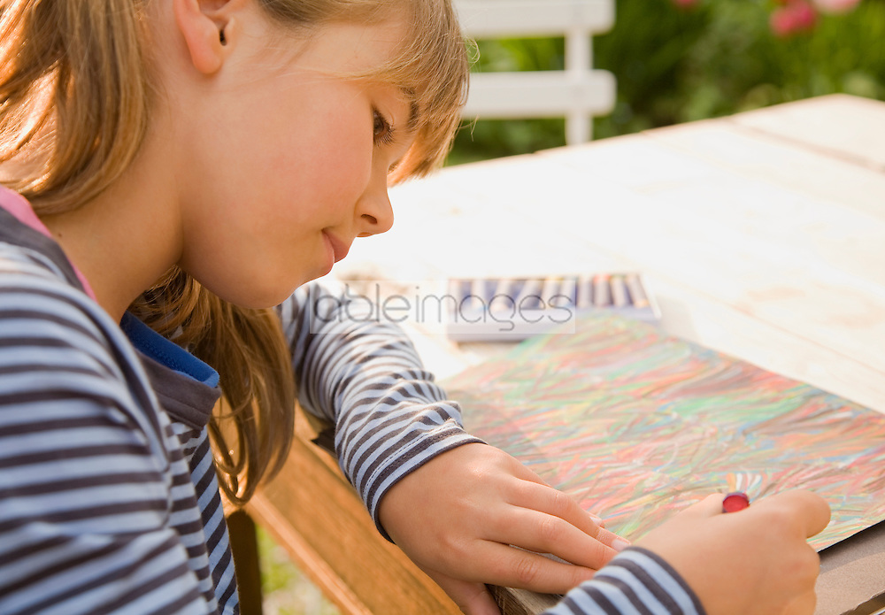 Teen girl drawing with crayons sitting at desk