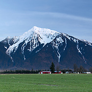 Agassiz farm field with Mount Cheam (Lhílheqey) in the background. Mount Cheam is a prominent mountain peak in the Fraser Valley of British Columbia. Located in the Canadian Cascade Range, the peak reaches 2104 meters/ 6903 feet in elevation.   Photographed from Agassiz, British Columbia, Canada.