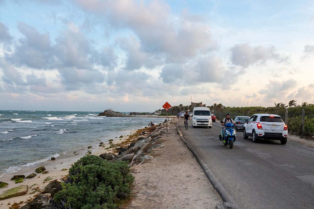 Tulum, Mexico - April 29, 2021: Cars, motorbikes, bicycles, and pedestrians use the coastal road in the hotel zone in Tulum, Mexico