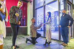 © Licensed to London News Pictures. 10/10/2020. Manchester, UK. In the queue for Sainsbury's , couple JONATHAN SCOTT (31) and LOUISE LAVERY (31) recreate the moment when Jonathan proposed to Louise earlier this evening . Fearing that a 2nd lockdown is imminent , the couple brought forward the celebration of their 2nd anniversary by a week to this evening and Jonathan proposed to Louise this evening .  People queue outside Sainsbury's on Deansgate as venues close and people come out on to the street . People out in pubs, bars and restaurants in Manchester City Centre ahead of the currently imposed daily 10pm curfew . Millions of people across the north of England are waiting to learn if the British Government will impose a regional lockdown on Monday (12th October 2020), as Coronovirus infection rates continue to rise rapidly . Photo credit: Joel Goodman/LNP