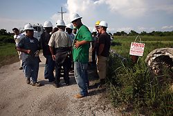 01 June 2010. New Orleans, Louisiana, USA.  <br /> Immigrant workers speaking barely a word of english file past after a day of oil clean up operations in and around Breton Sound Marina in Hopedale. An American supervisor following the men advised them not to stop and kept shouting 'vamanos,' encouraging the men to keep moving and not to be photographed.<br /> Photo; Charlie Varley/varleypix.com