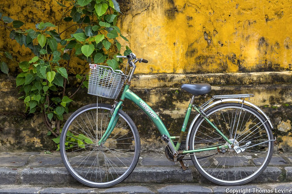 A green bicycle parked outside along a old yellow building in Old Town, Hoi An.