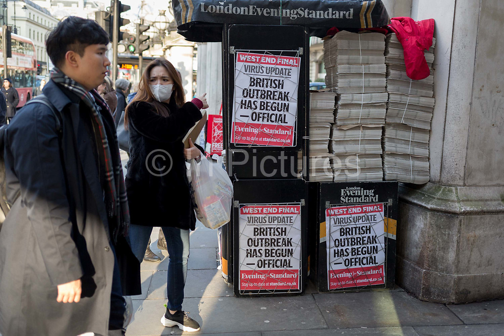 On the day that the UK Governments Chief Scientific Advisor, Sir Patrick Vallance said that the Coronavirus Covid-19 outbreak was now spreading person to person in the UK, a foreign visitor wearing a surgical face mask walks past a vendor and the latest news headline from the capitals London Evening Standard newspaper outside Charing Cross railway station, on 6th March 2020, in London, England.