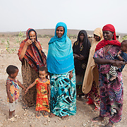 In Dowe district. Mothers and Traditional Birth Attendants (TBA). The three small girls have not been cut and Waliadoud, woman in blue, has got three daughters all not cut. Waliadoud lost her first baby girl due to FGM and has since stopped the practice. They are all advocates of stopping the FGM practice and the TBA's have stopped provided the service to women whom they help giving birth. Often its the TBA who will perform the FGM as well as act as midwife.. Action for Integrated Sustainable Development Association (AISDA) work in the AFAR region of Eastern Ethiopia, based in Delafagi. The Afars practise an old tradition of Female Genital Mutilation where the baby girls has her clitoris and labia cut away and her vagina sewn up. The day before her wedding day the girl is un-stiched ready for marriage. Its a brutal and barbaric tradition which AISDA is challenging with great effect, now more than a hundred girls in Dowe district have been saved from the knife and AISDA is now rolling out the scheme in Delafagi. Delafagi is where the oldest ever human remains have been found, the found is thought to be 4.5 mill years old.