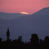 Israel, Golan Heights, Sun sets behind minaret in Arab village abandoned after 1967 Six Day War