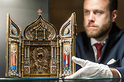 """© Licensed to London News Pictures. 01/06/2018. LONDON, UK. A Sotheby's technician presents """"An Imperial Silver-Gilt and Enamel Triptych Icon of the Feodorovskaya Mother of God"""", 1894, by Savelev Brothers (Est. GBP80-120k) at a preview of the Russian Pictures and Russian Works of Art, Fabergé & Icons sale which will take place at Sotheby's, New Bond Street on 5 June.  Photo credit: Stephen Chung/LNP"""